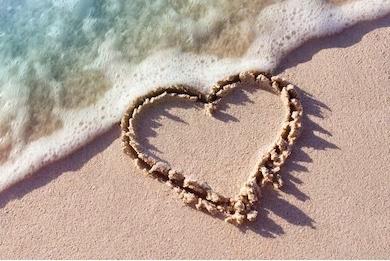 ビーチでの砂のハートマーク写真